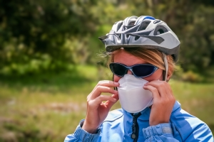 Woman wearing a bike helmet adjust her face mask before riding her bike.