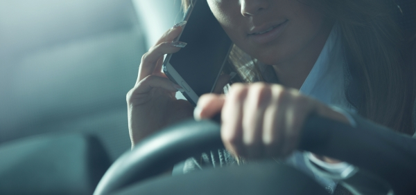 Woman driving while holding a mobile phone to her ear.